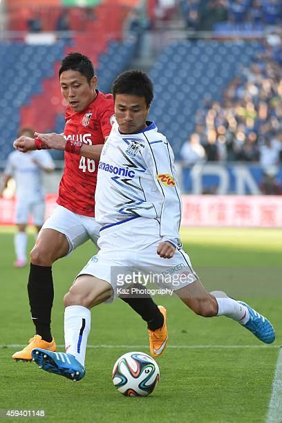 Yasuyuki Konno of Gamba Osaka passes the ball under the pressure from Ryota Moriwaki of Urawa Red Diamonds during the JLeague match between Urawa Red...