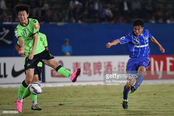Yasuyuki Konno of Gamba Osaka shoots while Jae Sung Lee of Jeonbuk Hyundai Motors tries to block during the AFC Champions League quarter final match...