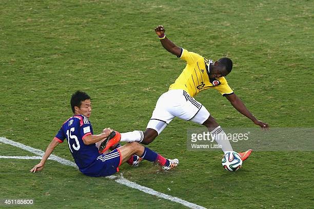 Yasuyuki Konno of Japan fouls Adrian Ramos of Colombia during the 2014 FIFA World Cup Brazil Group C match between Japan and Colombia at Arena...