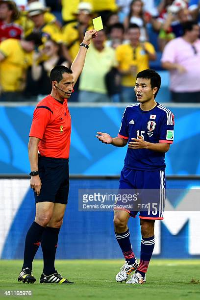 Yasuyuki Konno of Japan is shown an yellow card by referee Pedro Proenca during the 2014 FIFA World Cup Brazil Group C match between Japan and...