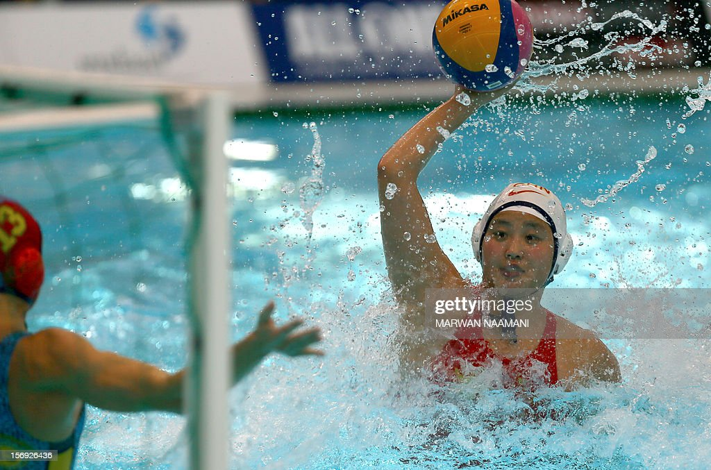 Yating Sun (L) of China attempts to score against Alexandra Zharkova, goal keeper, of Kazakhstan during the two teams water polo game at the 9th Asian Swimming Championships in Dubai, on November 25 2012. China won the gold medal after beating Kazakhstan 13-8. AFP PHOTO/MARWAN NAAMANI