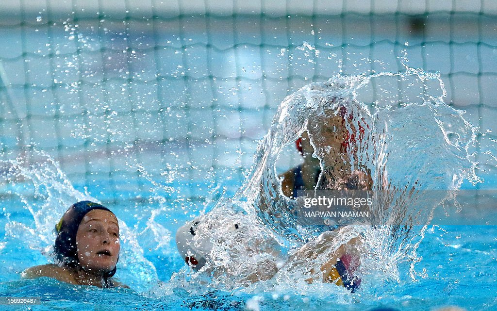Yating Sun (R) of China vies for the ball against Anna Zubkova of Kazakhstan as she tries to block the shot during the two teams water polo game at the 9th Asian Swimming Championships in Dubai, on November 25 2012. China won the gold medal after beating Kazakhstan 13-8.
