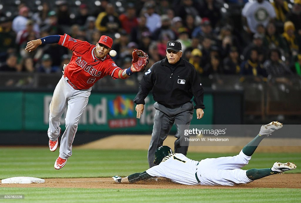 Yaunel Escobar #6 of the Los Angeles Angels of Anaheim leaps to keep the ball from going into left field as Billy Burns #1 of the Oakland Athletics steals third base in the bottom of the third inning at O.co Coliseum on April 12, 2016 in Oakland, California.
