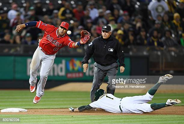 Yaunel Escobar of the Los Angeles Angels of Anaheim leaps to keep the ball from going into left field as Billy Burns of the Oakland Athletics steals...
