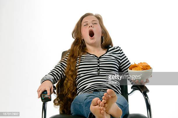 yawning teenage redhead in chair with crisps and remote control