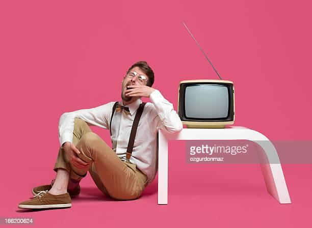 あくびをする若い男性の隣に座って TV