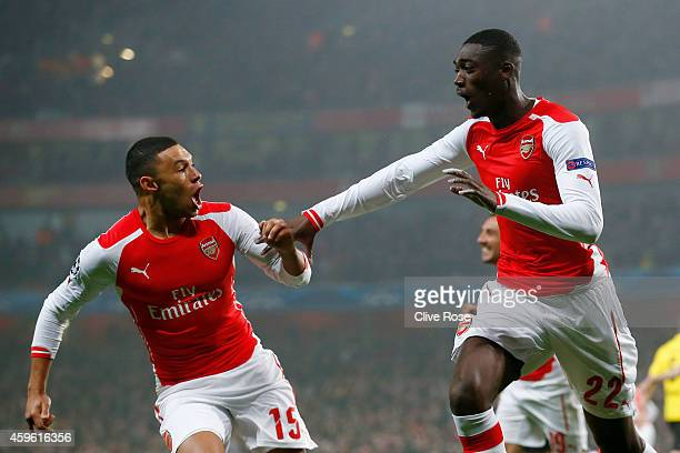 Yaya Sanogo of Arsenal celebrates with teammate Alex OxladeChamberlain after scoring the opening goal during the UEFA Champions League Group D match...