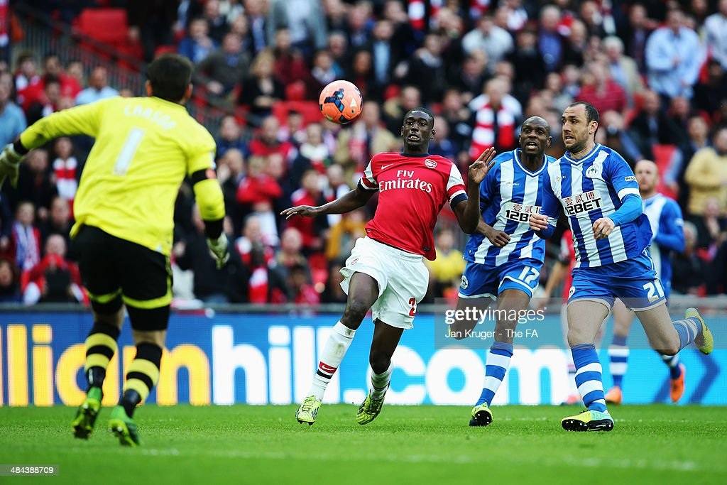 Yaya Sanogo of Arsenal is challenged by Emmerson Boyce of Wigan Athletic and Ivan Ramis of Wigan Athletic during the FA Cup SemiFinal match between...