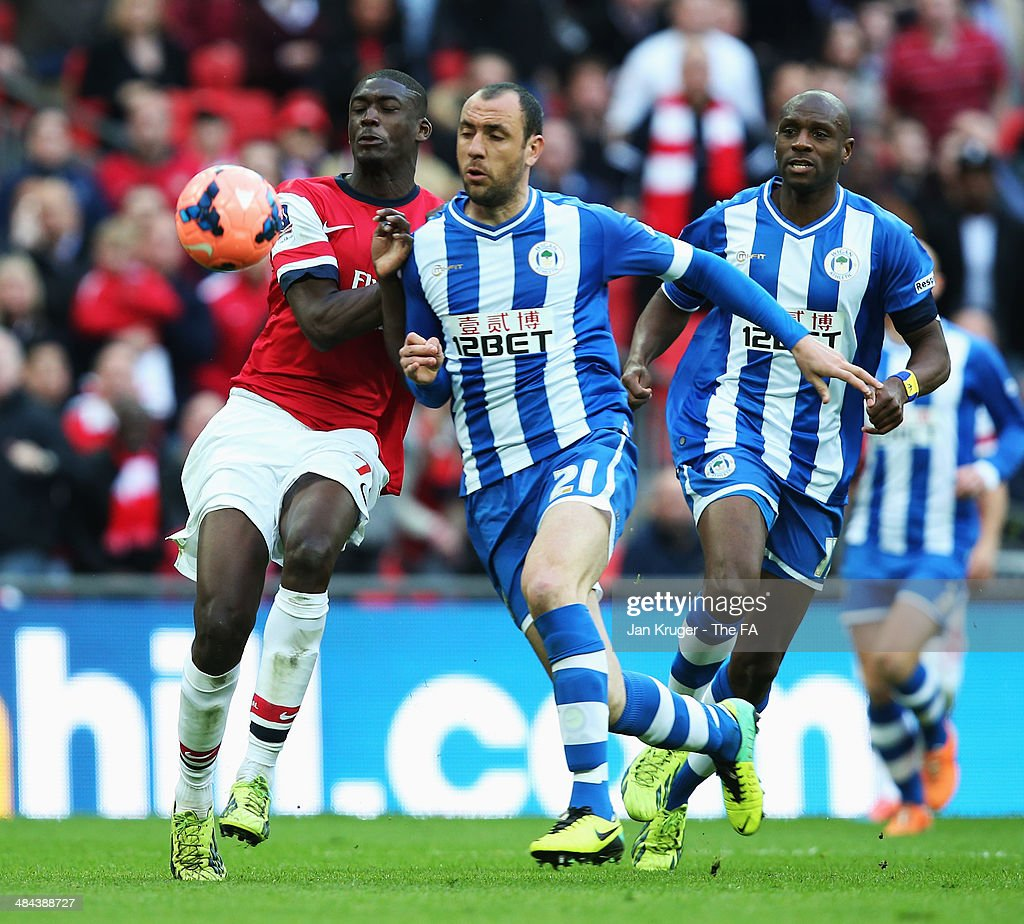 Yaya Sanogo of Arsenal is challenged by Ivan Ramis of Wigan Athletic during the FA Cup SemiFinal match between Wigan Athletic and Arsenal at Wembley...