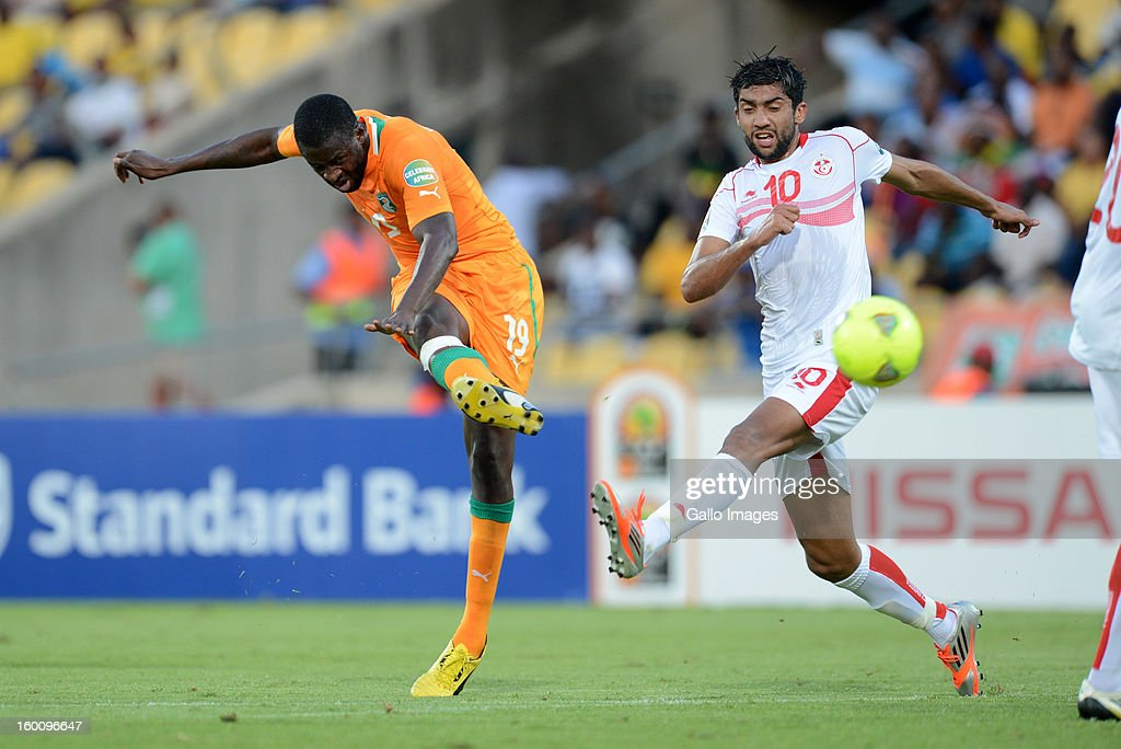 AFRICA - JANUARY 26, Yaya Toure of Ivory Coast scores a goal under pressure from Oussama Darragi of Tunisia during the 2013 African Cup of Nations match between Ivory Coast and Tunisia at Royal Bafokeng Stadium on January 26, 2013 in Rustenburg, South Africa.