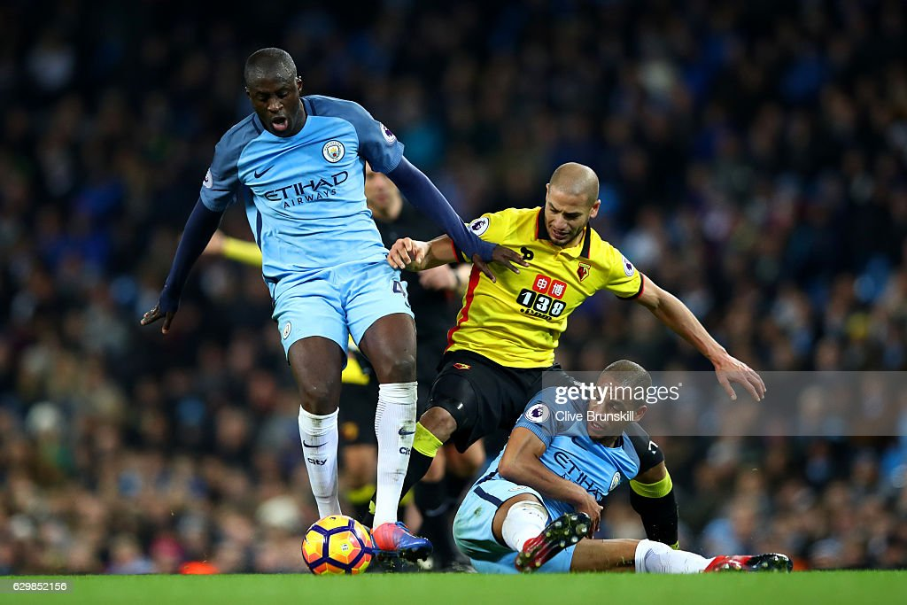 Yaya Toure of Manchester City (L) and Adlene Guedioura of Watford (C) and Fernando of Manchester City (R) battle for possession during the Premier League match between Manchester City and Watford at Etihad Stadium on December 14, 2016 in Manchester, England.