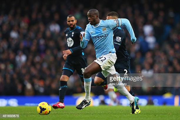 Yaya Toure of Manchester City breaks past Kyle Walker and Sandro of Tottenham Hotspur on the way to setting up Sergio Aguero for their team's fourth...