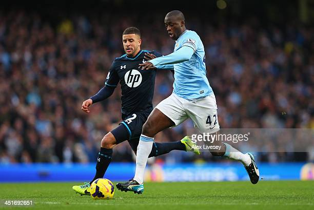 Yaya Toure of Manchester City breaks past Kyle Walker of Tottenham Hotspur on the way to setting up Sergio Aguero for their team's fourth goal during...