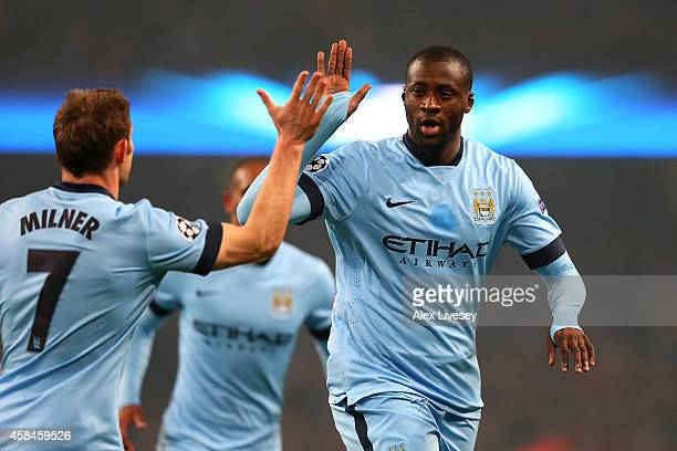 Yaya Toure of Manchester City celebrates scoring his team's first goal with James Milner during the UEFA Champions League Group E match between...