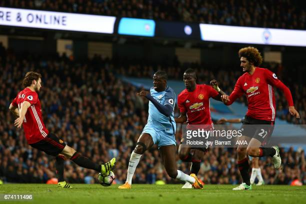 Yaya Toure of Manchester City competes with Eric Bailly and Daley Blind of Manchester United during the Premier League match between Manchester City...