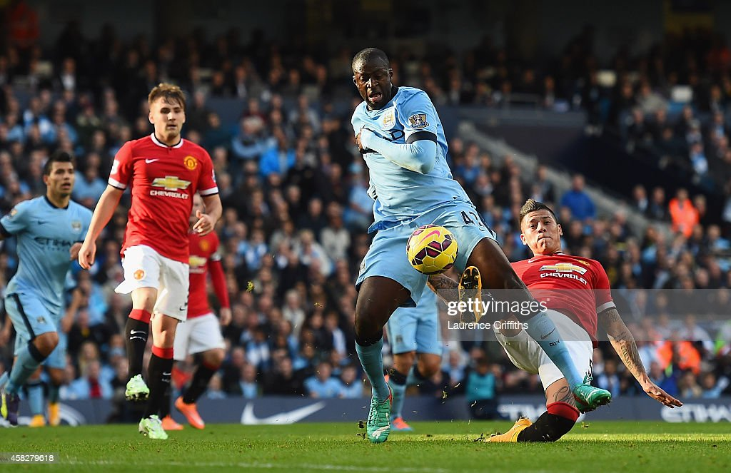 Yaya Toure of Manchester City goes down in the area after a challenge from Marcos Rojo of Manchester United during the Barclays Premier League match between Manchester City and Manchester United at Etihad Stadium on November 2, 2014 in Manchester, England.