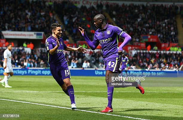 Yaya Toure of Manchester City is congratulated by teammate Jesus Navas of Manchester City after scoring his team's third goal during the Barclays...
