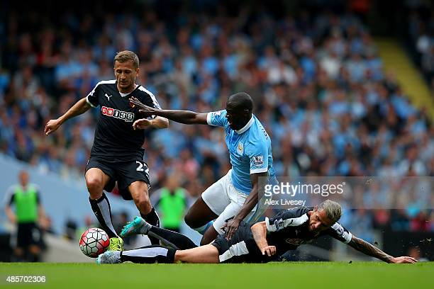 Yaya Toure of Manchester City is tackled by Valon Berami of Watford during the Barclays Premier League match between Manchester City and Watford at...
