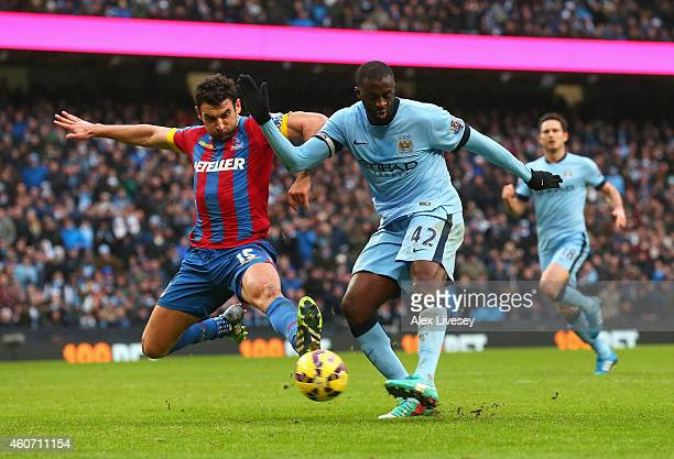 Yaya Toure of Manchester City scores his goal challenged by Mile Jedinak of Crystal Palace during the Barclays Premier League match between...