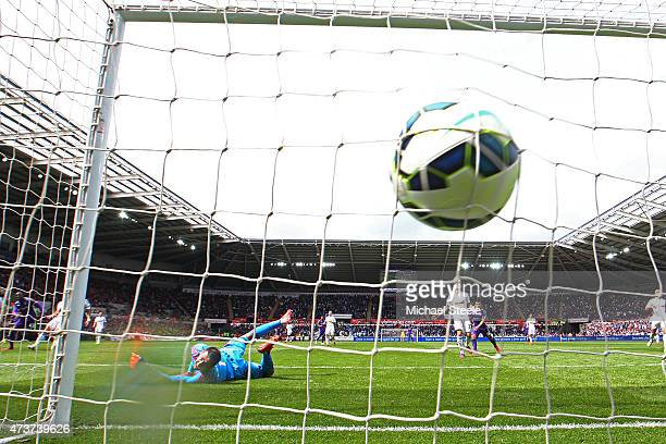 Yaya Toure of Manchester City scores is team's third goal past the outstretched Lukasz Fabianski of Swansea City during the Barclays Premier League...