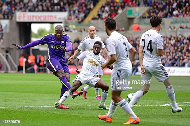 Yaya Toure of Manchester City scores the opening goal past the challenge from Nathan Dyer of Swansea City during the Barclays Premier League match...