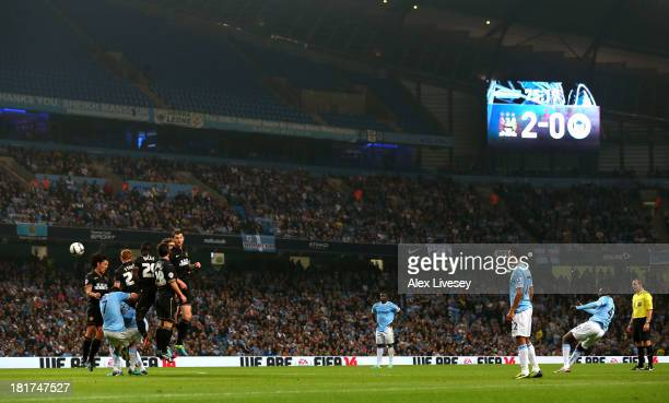 Yaya Toure of Manchester City scores the third goal from a free kick during the Capital One Cup third round match between Manchester City and Wigan...