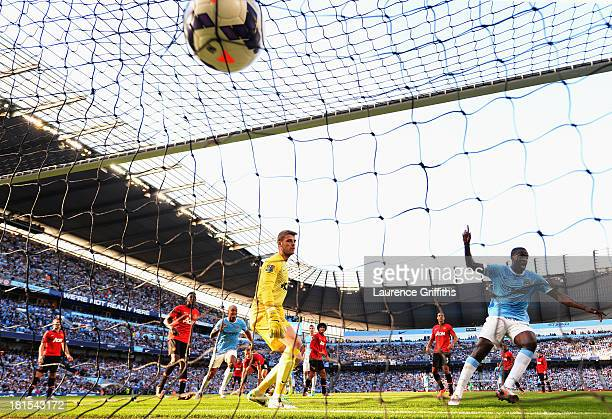 Yaya Toure of Manchester City scores their second goal as goalkeeper David De Gea of Manchester United looks on during the Barclays Premier League...