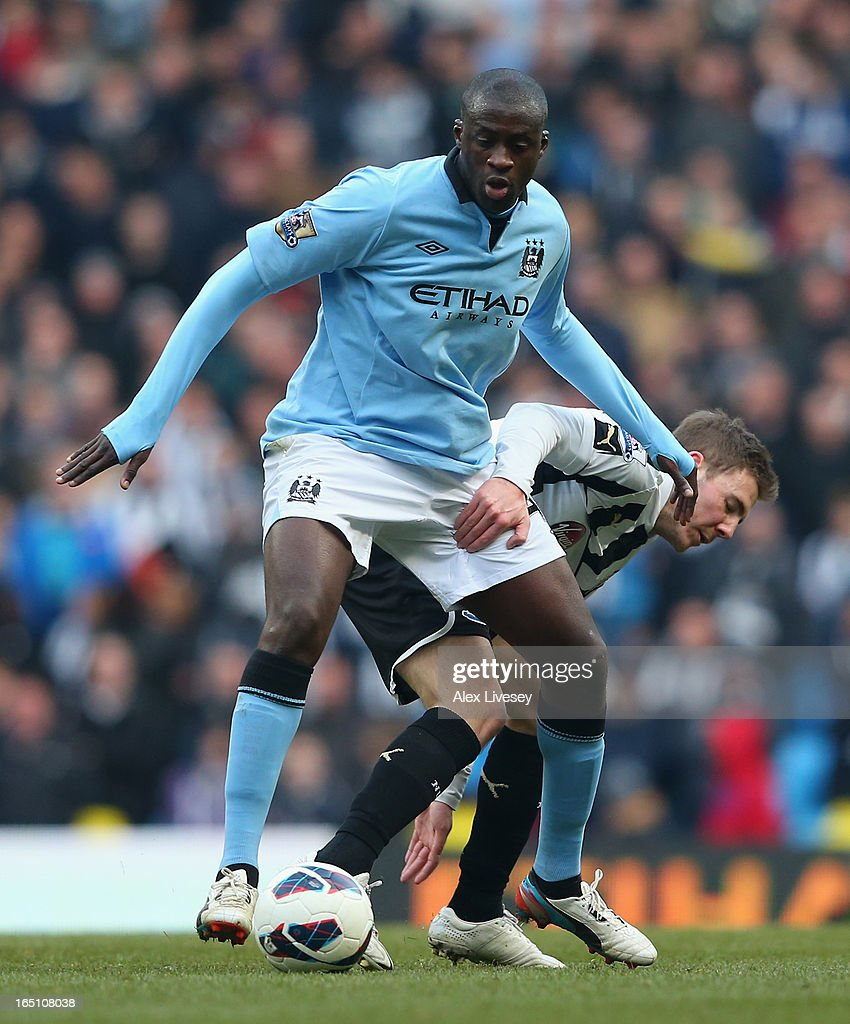 Yaya Toure of Manchester City tussles for posession with <a gi-track='captionPersonalityLinkClicked' href=/galleries/search?phrase=Dan+Gosling+-+Jugador+de+f%C3%BAtbol&family=editorial&specificpeople=8957793 ng-click='$event.stopPropagation()'>Dan Gosling</a> of Newcastle United during the Barclays Premier League match between Manchester City and Newcastle United at the Etihad Stadium on March 30, 2013 in Manchester, England.