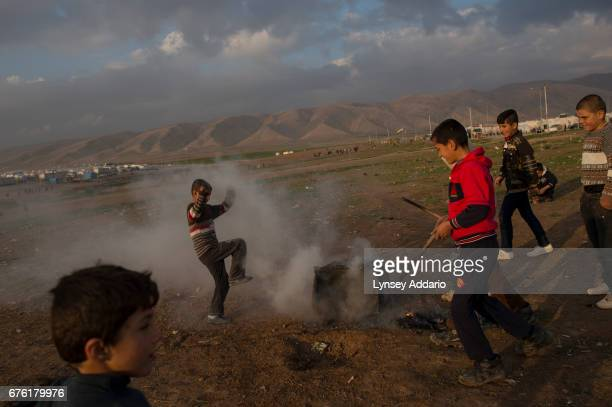 Yazidi children play with fire in the Sharia camp outside dohuk January 24 2016 Yazidismany of whom have suffered at the hands of ISISare living in...
