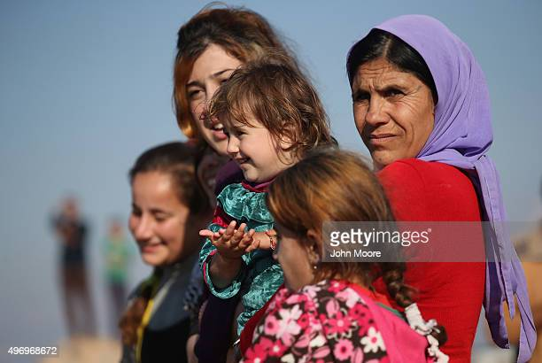 Yazidi refugees watch as othes celebrate news of the liberation of their homeland of Sinjar from ISIL extremists while at a refugee camp on November...
