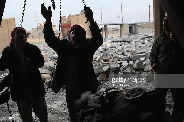 Yazidis work to lift an engine to salvage it from the rubble of an auto repair shop destroyed by an airstrike on November 16 2015 in Sinjar Iraq...