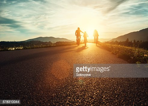 Сyclists family traveling on the road at sunset : Foto de stock