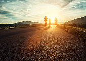 Сyclists family traveling on the road at sunset