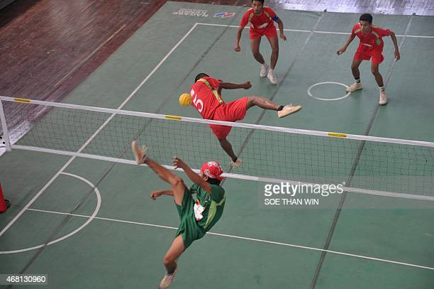 Ye Thura of the Ministry of Defence team blocks a strike as Kyi Linn Phyo of the 16/1 team kicks the ball during the 4TV Cup match at the Myanmar...