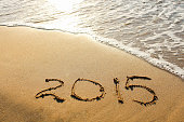 year 2015 written on sandy beach