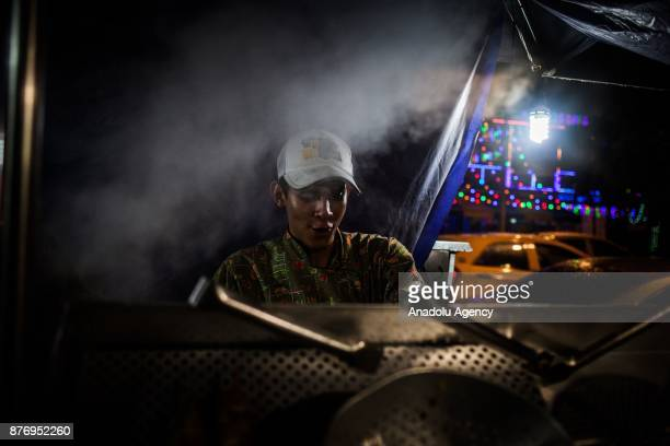 24 year old Abraham cooks traditional Venezuelan food 'Arepas' at the streets in Medellin Colombia on November 20 2017 After a long trip from their...