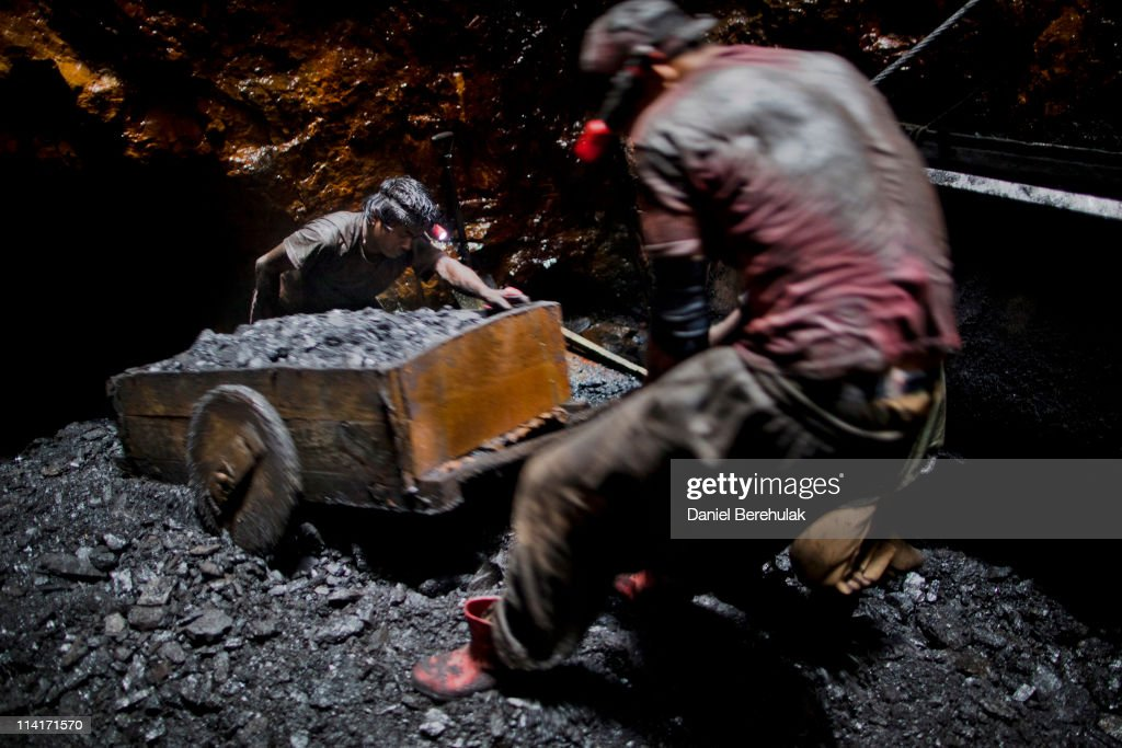 20 year old Anil Basnet pushes a coal cart, as he and a fellow worker pull coal out from the rat hole tunnel 300 ft below the surface on April 13, 2011 near the village of Latyrke near Lad Rymbai, in the district of Jaintia Hills, India. The Jaintia hills, located in India's far North East state of Meghalaya, miners descend to great depths on slippery, rickety wooden ladders. Children and adults squeeze into rat hole like tunnels in thousands of privately owned and unregulated mines, extracting coal with their hands or primitive tools and no safety equipment. Workers can earn as much as 150 USD per week or 30,000 Rupees per month, significantly higher than the national average of 15 USD per day. After traversing treacherous mountain roads, the coal is delivered to neighbouring Bangladesh and to Assam from where it is distributed all over India, to be used primarily for power generation and as a source of fuel in cement plants. Many workers leave homes in neighbouring states, and countries, like Bangladesh and Nepal, hoping to escape poverty and improve their quality of life. Some send money back to loved ones at home, whilst many others squander their earnings on alcohol, drugs and prostitution in the dusty, coal mining towns like Lad Rymbai. Some of the labor is forced, and an Indian NGO group, Impulse, estimates that 5,000 privately-owned coal mines in Jaintia Hills employed some 70,000 child miners. The government of Meghalaya refuted this figure, claiming that the mines had only 222 minor workers. Despite the ever present dangers and hardships, children, migrants and locals flock to the mines hoping to strike it rich in India's wild east.