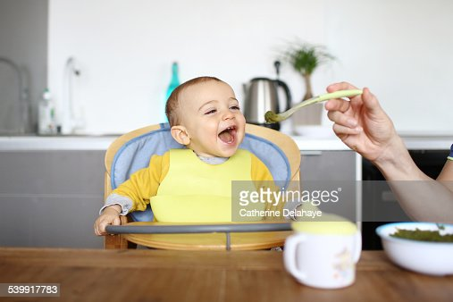 A 1 year old baby boy eating in his high chair