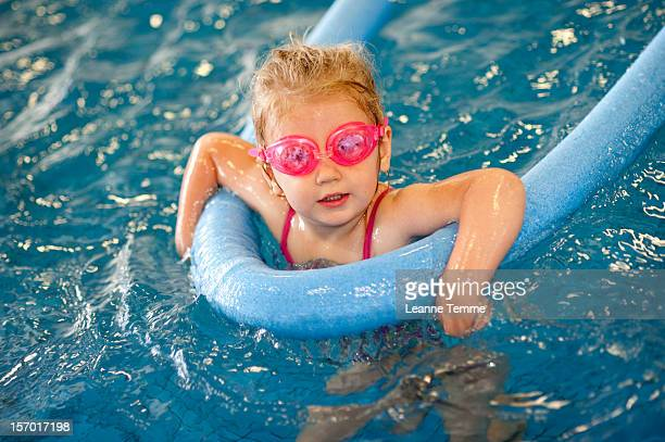 3 year old blonde girl holding noodle toy  in pool