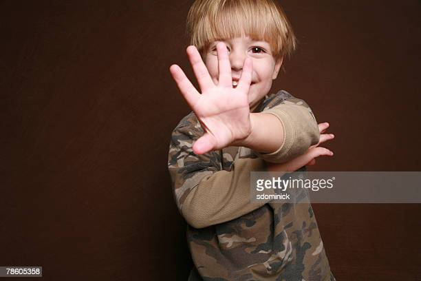 4 year old boy being playful and putting his hand out to hide his face.