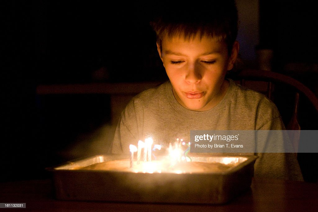 11 year old boy blowing out birthday candles : Stock Photo