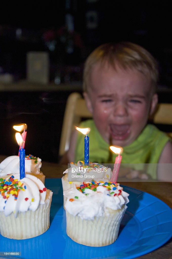 A 1 year old boy crying at his birthday party : Stock Photo
