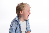 A profile view of a two year old boy crying. Shot in the studio on a white, seamless backdrop.