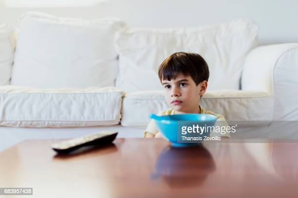 6 year old boy eating breakfast in front of the television