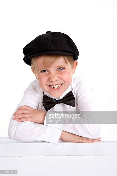A 7 year old boy in a bow tie and cap and a big grin.