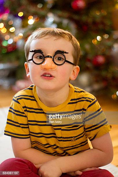 4 year old boy in false nose in front of Xmas Tree