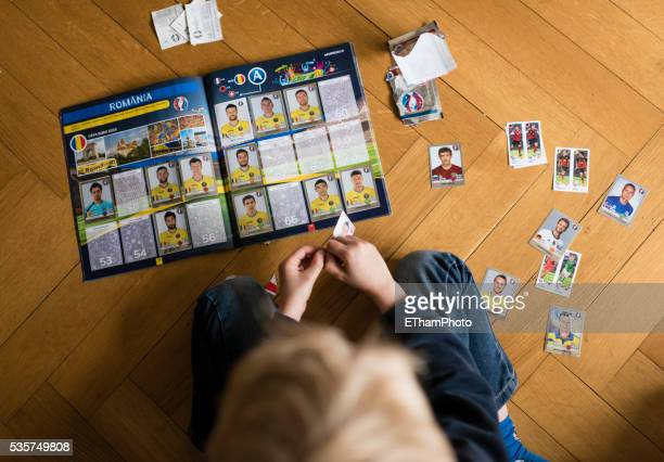 8 year old boy pasting soccer trading cards into his scrapbook