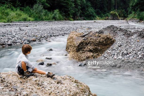 7 year old boy sitting on large rock by creek in rocky canyon in Austria.