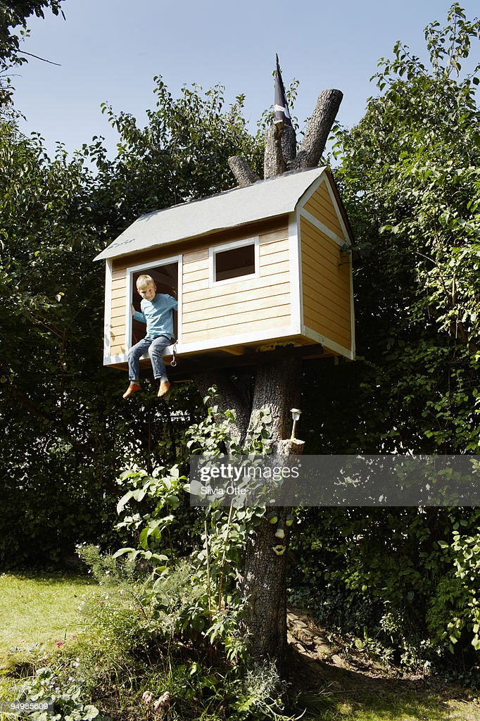 7 year old boy smiling out of his tree house : Stock Photo