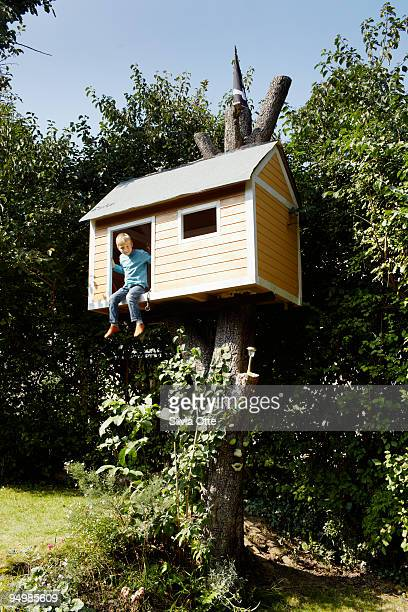 7 year old boy smiling out of his tree house